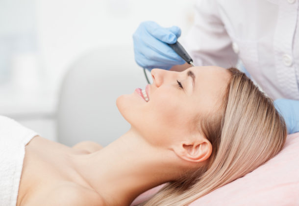 Close up of arms of experienced beautician undergoing laser skin treatment of skin on female face. The young woman is lying and smiling